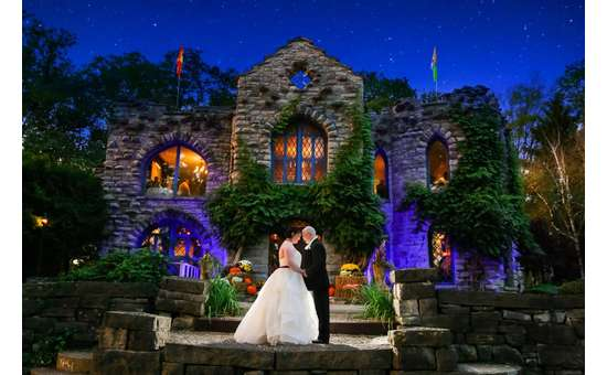 bride and groom embracing outside a stone castle like building