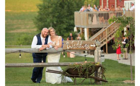 bride and groom leaning on a wooden fence