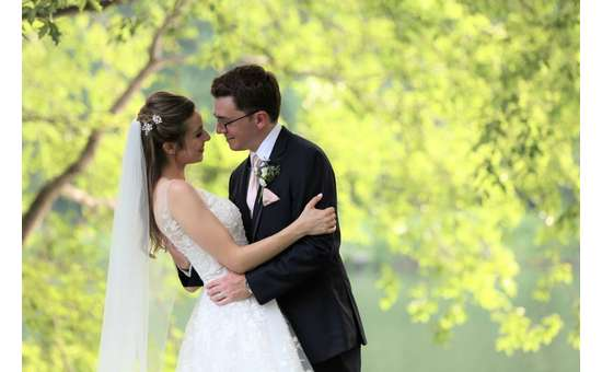 bride and groom embracing outdoors near tree