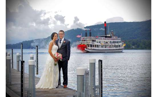 bride and groom standing on boat dock with steamboat in the background