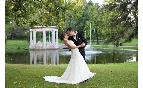 bride and groom in a park with a pond in the background