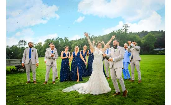 bride, groom, and wedding party celebrating with champagne outdoors