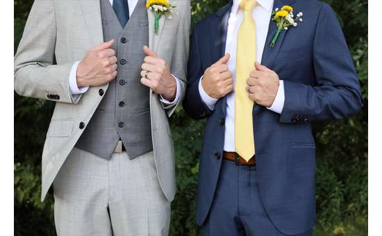 two men wearing suits for a wedding