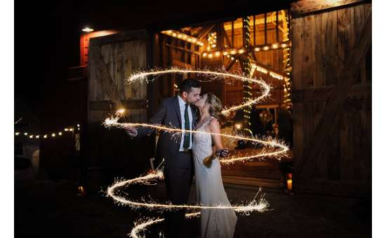 bride and groom kissing outside rustic barn while sparkles are around them