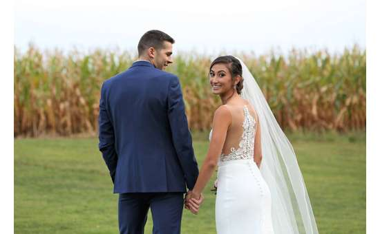 bride and groom walking towards a cornfield