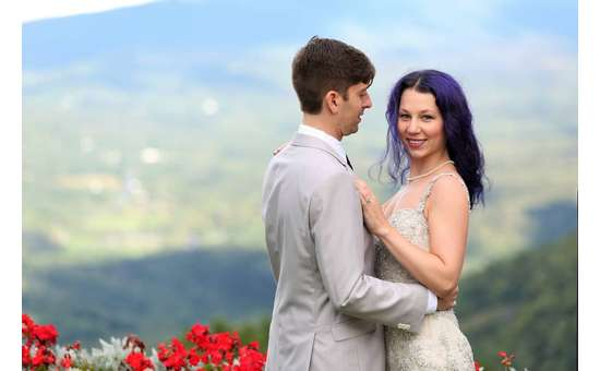 bride and groom embracing with a mountain view in the background