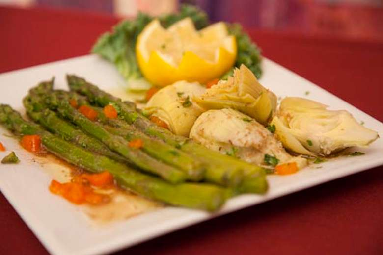 plate of fresh bright green asparagus served with artichoke hearts and a lemon cut into a flower