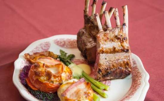 rack of lamb served with stuffed tomato,mushroom and artichoke with fresh asparagus