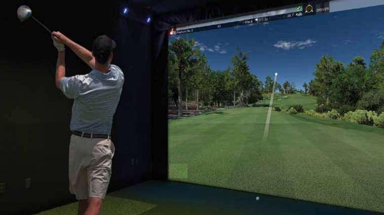 man swinging golf club facing a golf simulator screen