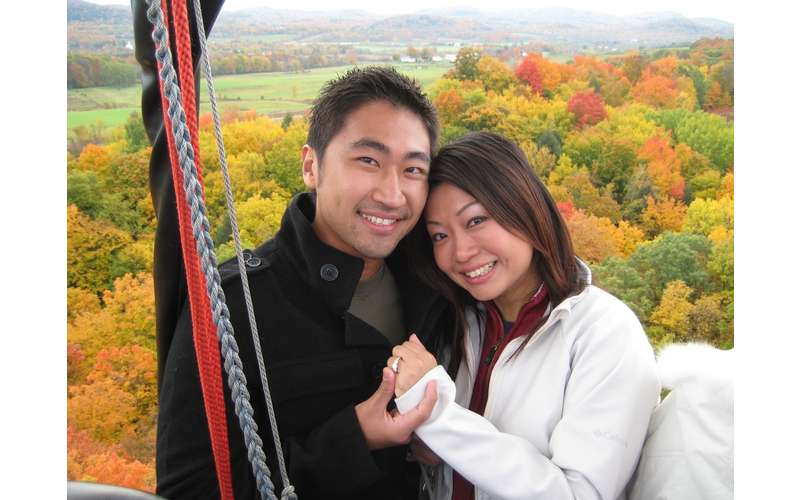 a man and woman holding hands in a hot air balloon