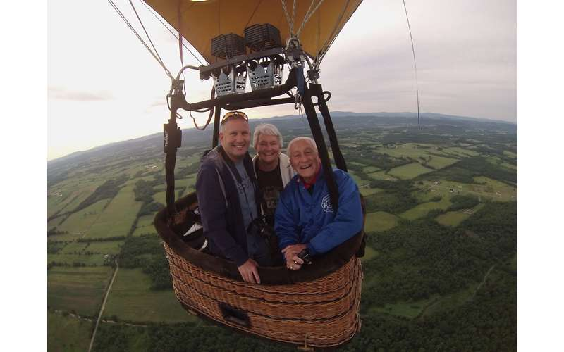 three people in a hot air balloon basket
