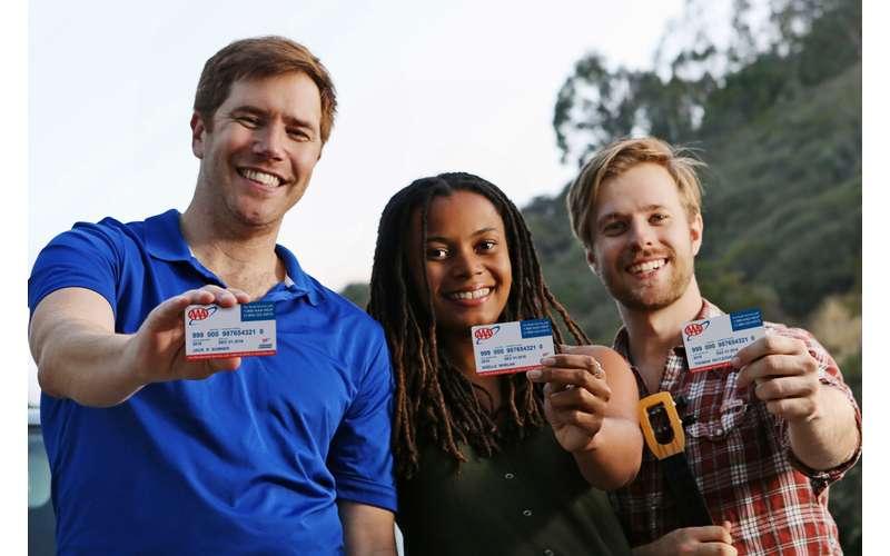 three people holding up aaa membership cards