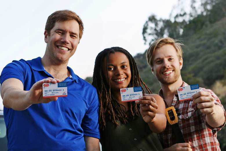 three people holding up aaa membership cards