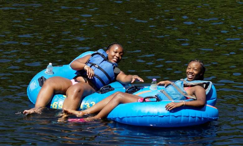 two girls hanging out in blue tubes on a river