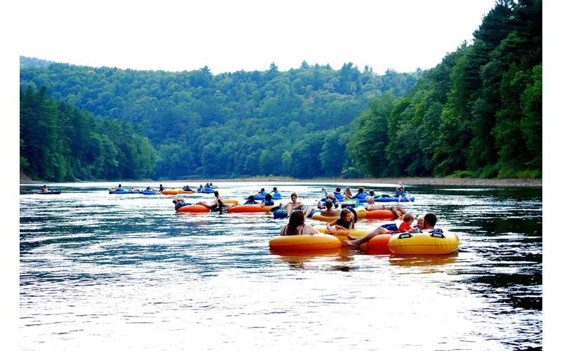 large group of people in yellow and blue tubes floating down the river