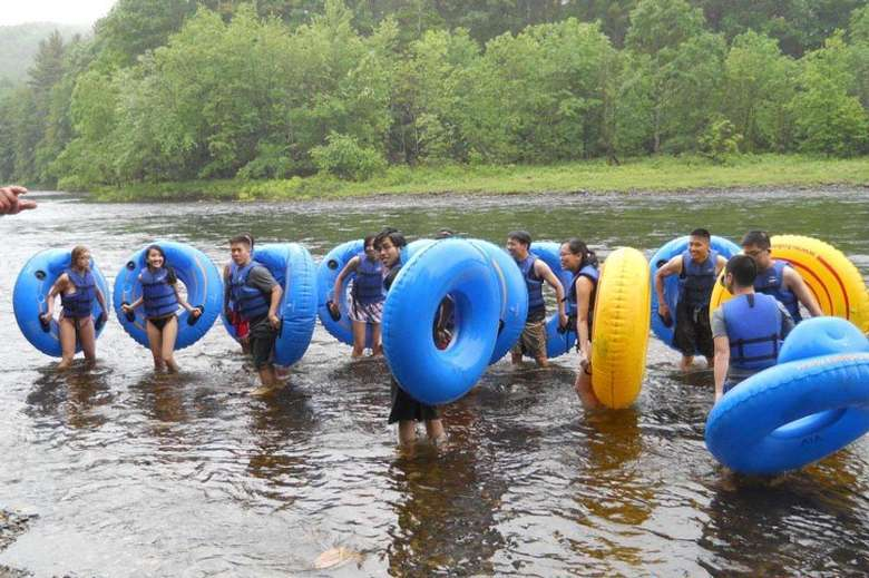 group of people standing up in a river holding up tubes