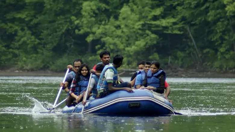 a fairly large group of people in a single raft on a river