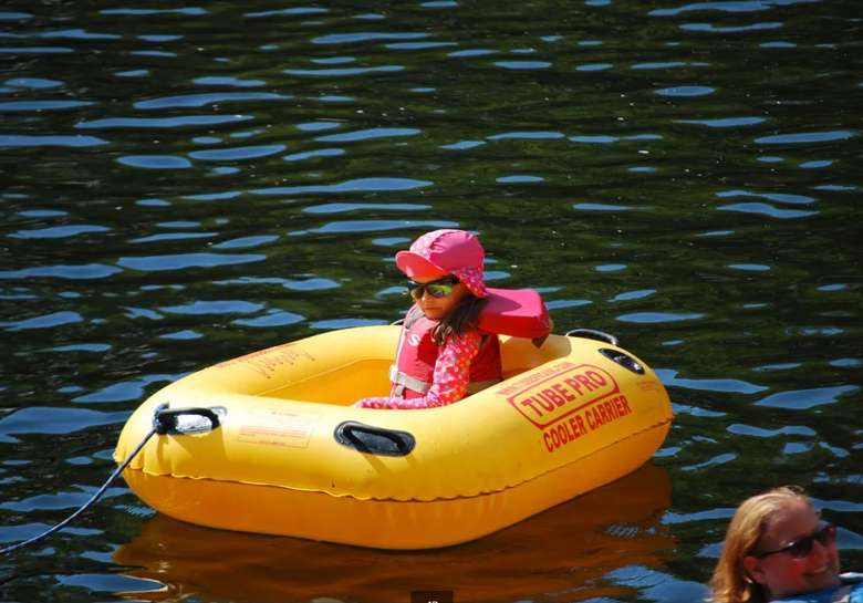 a young girl sitting in a yellow raft tube