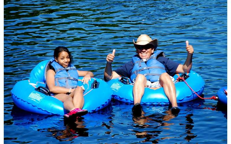 girl and a man sitting in separate blue tubes on a river, the man is giving a thumbs up