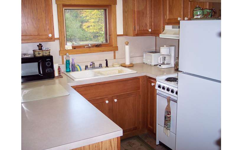 a small kitchen with wooden cabinets and a white refrigerator