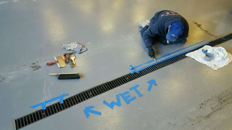 man repairing cement on the floor of a building