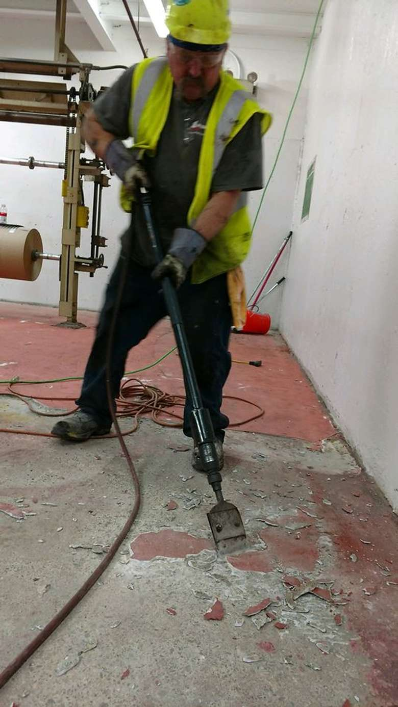 man using machinery to blast up old flooring