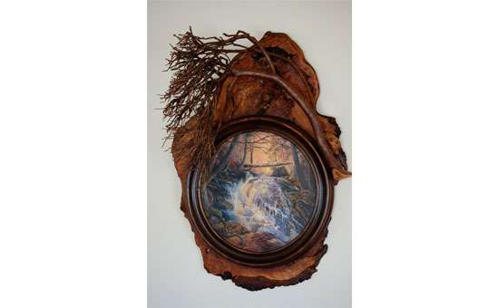 a painting of a river within a circular rustic frame