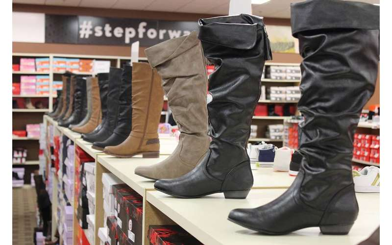 a line of boots on display in a shoe store
