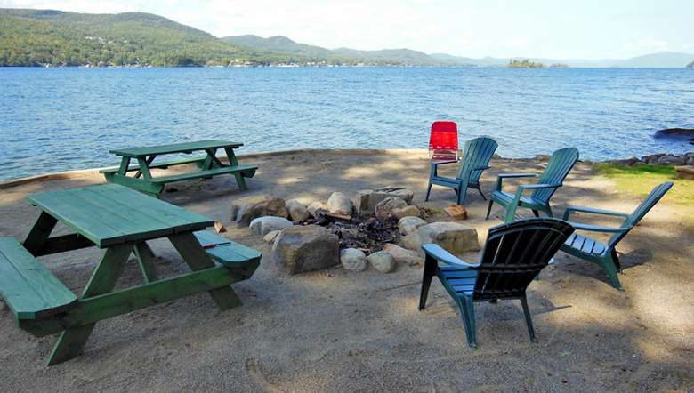picnic tables and chairs around a fire pit