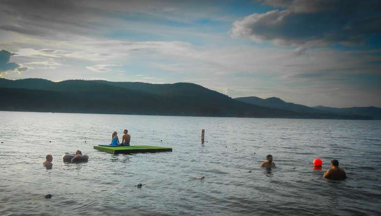 people swimming in the lake, couple sitting on green dock