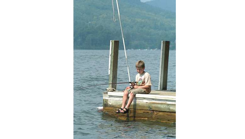little boy fishing off a dock