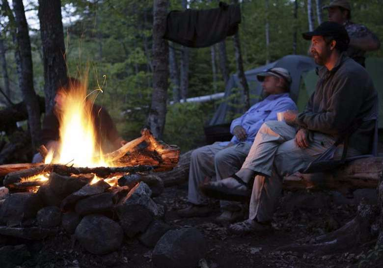 two men sitting in front of a fire at a campsite at dusk