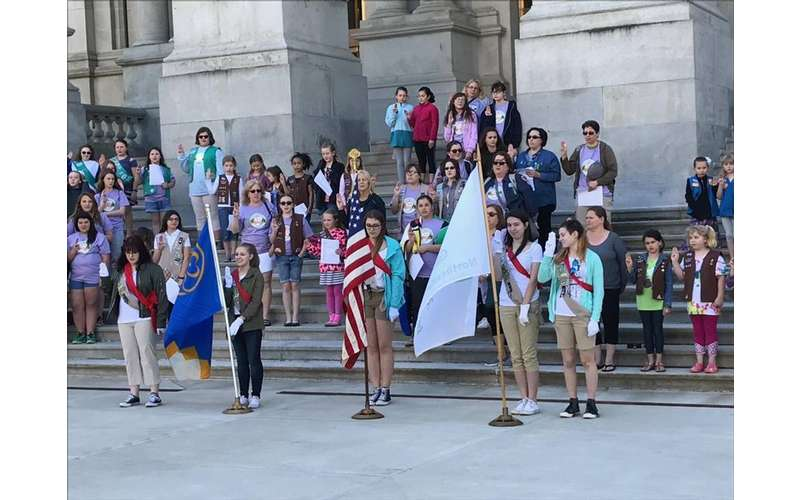 large group of girl scouts and people standing on steps