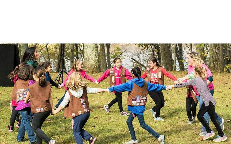 a group of girl scouts holding hands in a circle