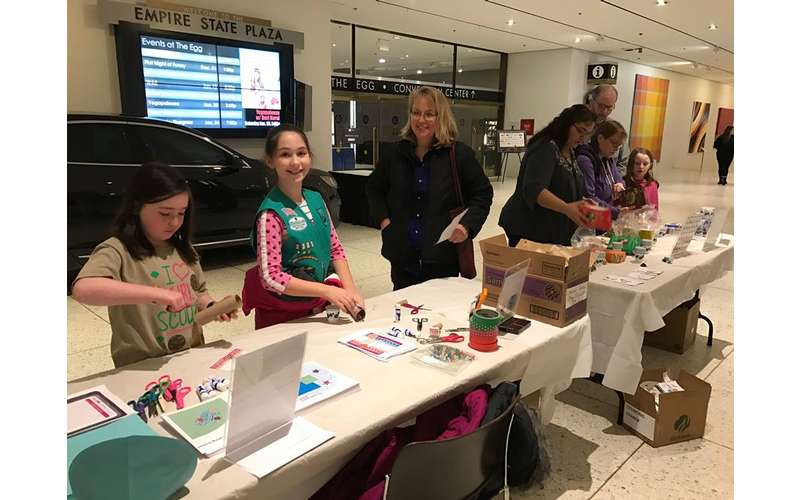 girl scouts and volunteers behind cookie tables