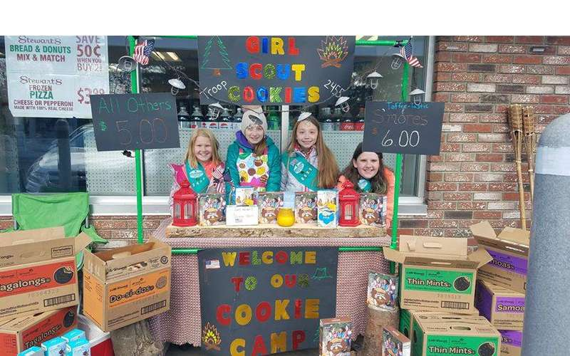 four girl scouts behind a cookie booth