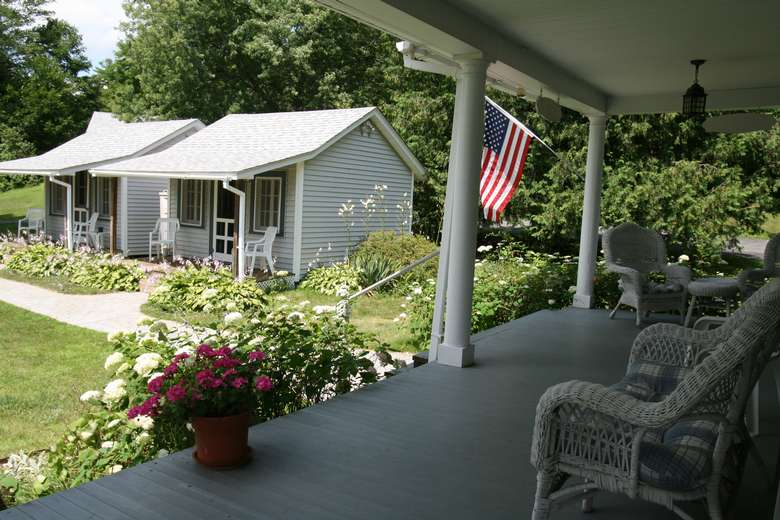 view of sheds from the porch, white whicker furniture