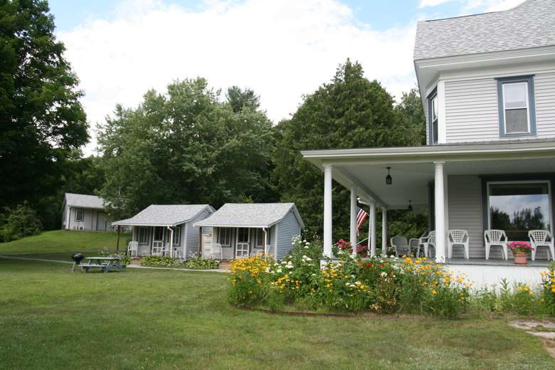 quaint house with wraparound porch, two cute sheds or small cottages