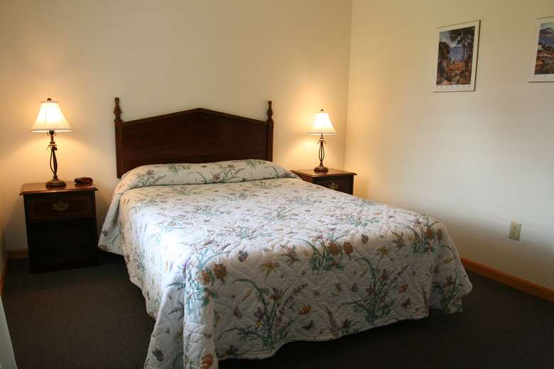 bed with floral bedspread, two nightstands with lamps