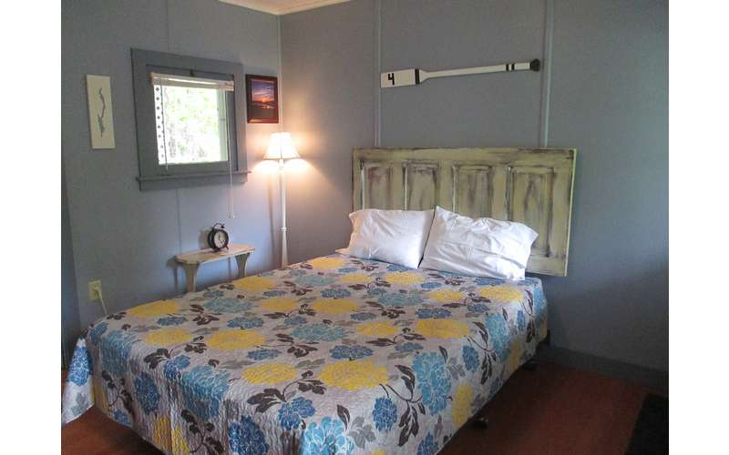 bed with blue and yellow floral bedspread