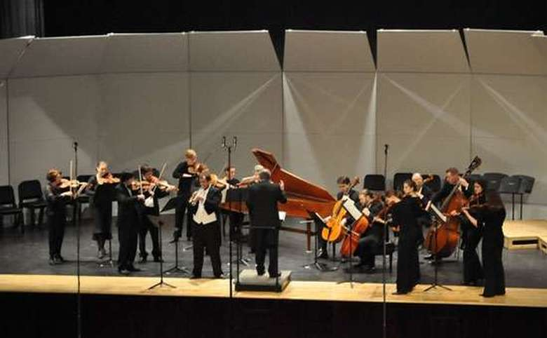 People standing playing string instruments on stage