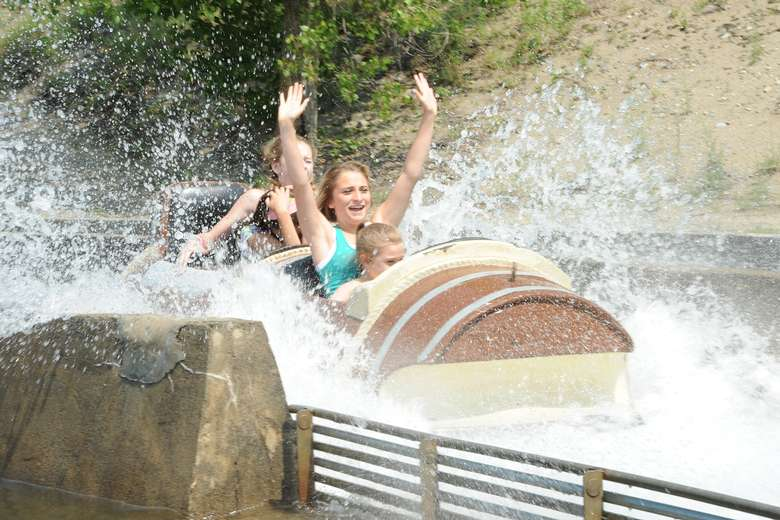 two adults and two kids splashing into the end of the desperado plunge ride