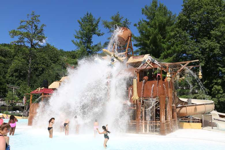 a huge bucket of water being dumped on people at a water park