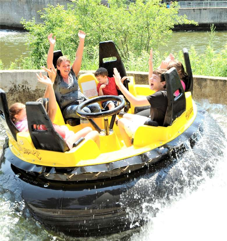 group of people on a black and yellow raft riding the raging river