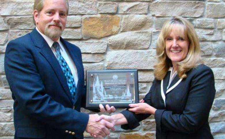 Woman and man shaking  hands holding award