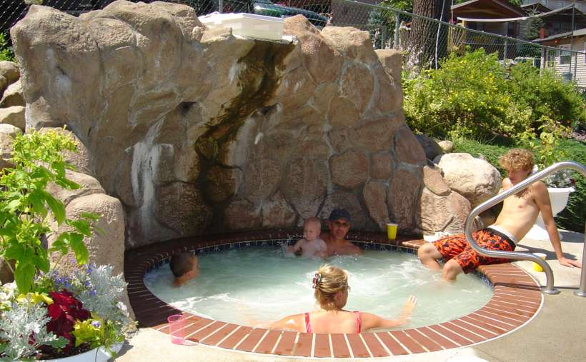 people in an outdoor hot tub that's in the ground like an indoor pool