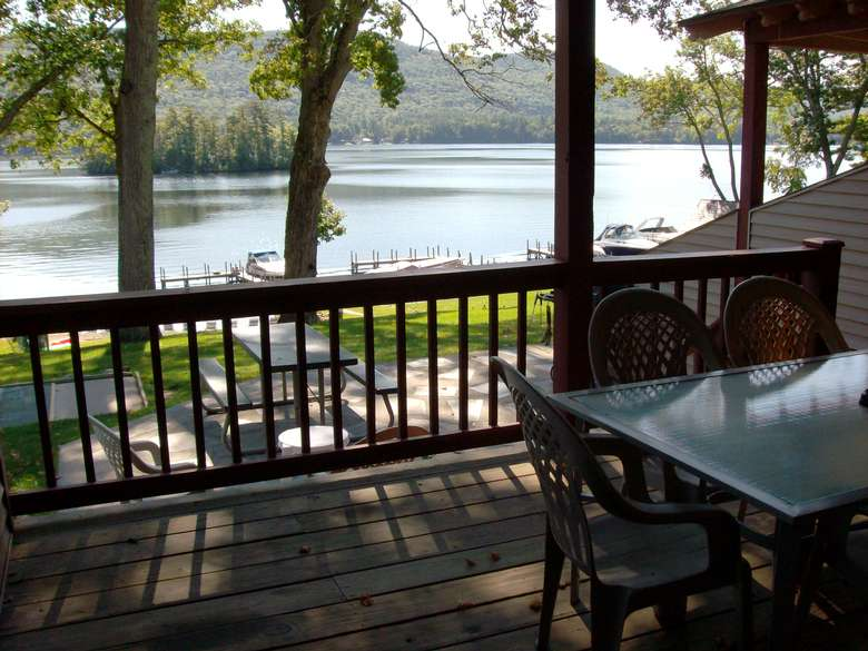 view from a deck of water and picnic tables