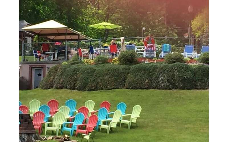 colorful Adirondack chairs, pool in the background