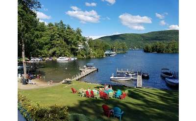 somewhat aerial view of colorful lawn chairs, water, dock, boat, mountains