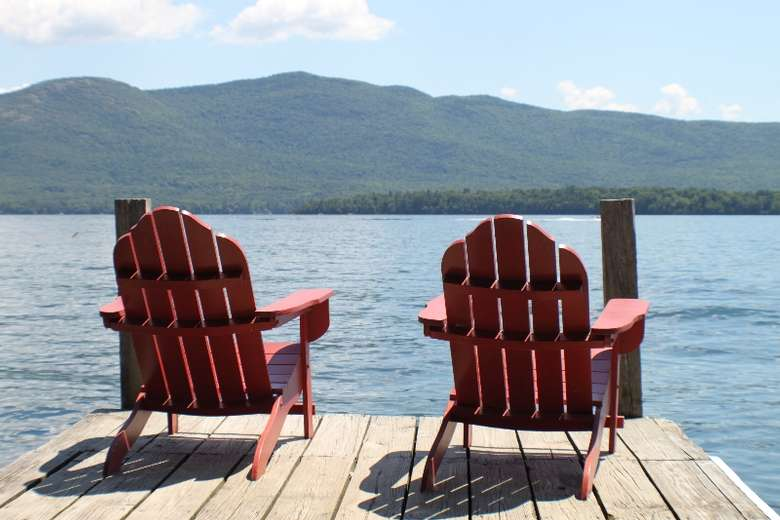 two red adirondack chairs on a dock overlooking the lake with mountains in the background